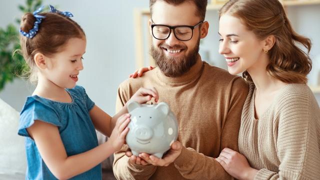 Family putting money away into piggy bank