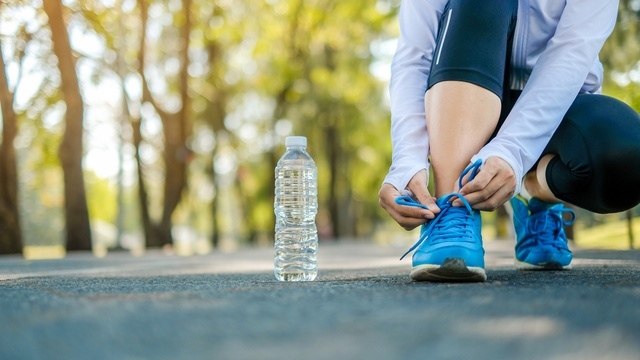 Female runner tying her laces next to a bottle of water