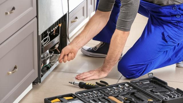 man repairing a fridge