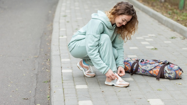 Woman in sportswear tying her shoelaces