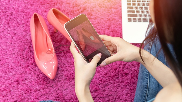 Woman taking a picture of a pair of heels to sell online.
