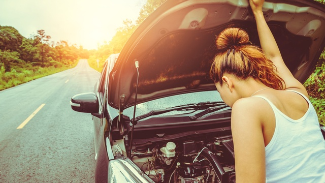 Woman on the side of the road checking engine oil levels of car