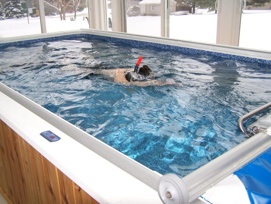 swimming in an indoor Original Endless Pool during a winter snow