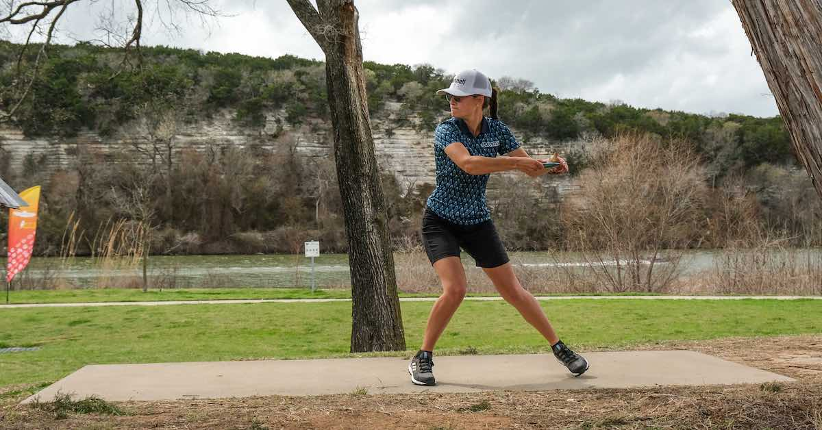A woman running up to throw a disc with a river and sheer rock wall in the background