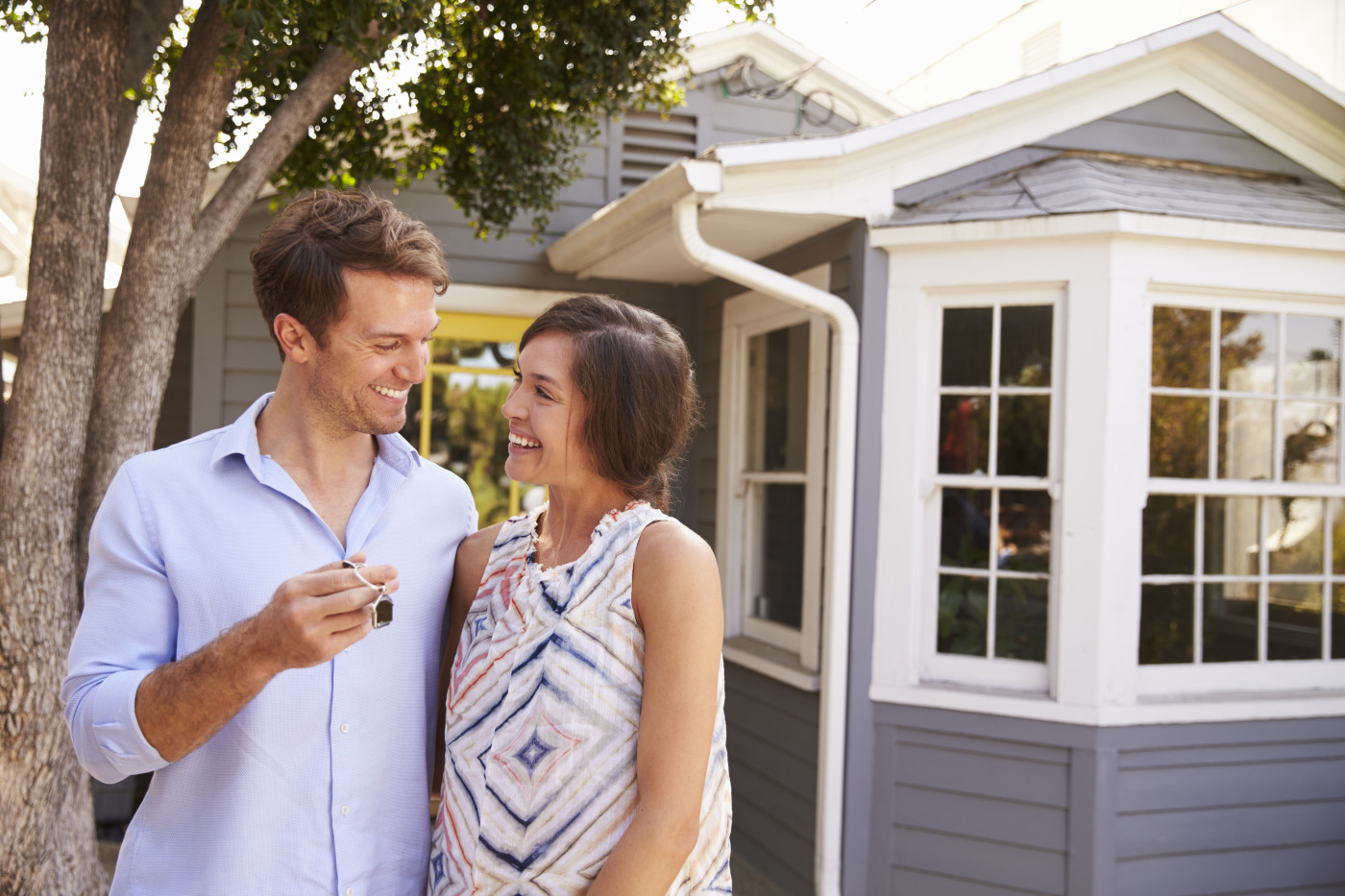 couple smiling with new house keys in hand