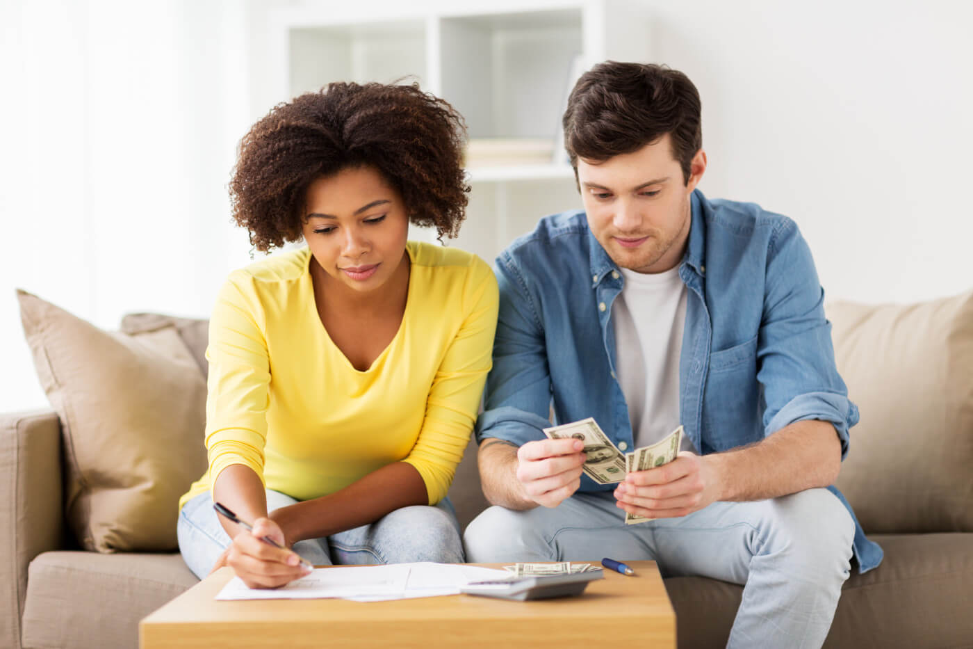 couple with papers and calculator looking for a savings account