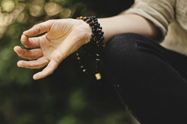 elderly woman's hand doing ohm mudra, wearing mala beads at outdoor nursing home yoga class