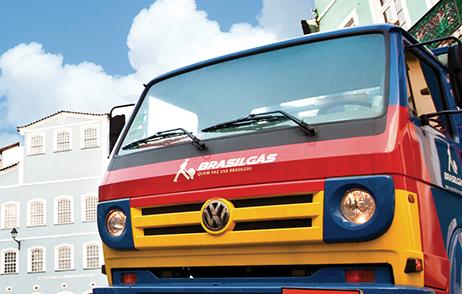 Foto de 02 caminhões da Ultragaz mostrando na maior parte da foto a frente dos caminhões em um posto da Ultragaz. Os caminhões possuem a pintura na cor da marca sendo elas o azul, o vermelho e o amarelo.