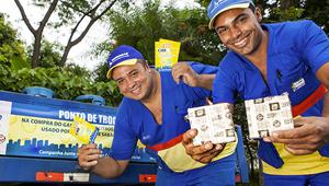Foto de dois funcionários da ultragaz vestidos com uniforme nas cores azul, amarela e vermelha. Ambos segurando presentes e sorrindo. Ao fundo árvores e botijões azuis.