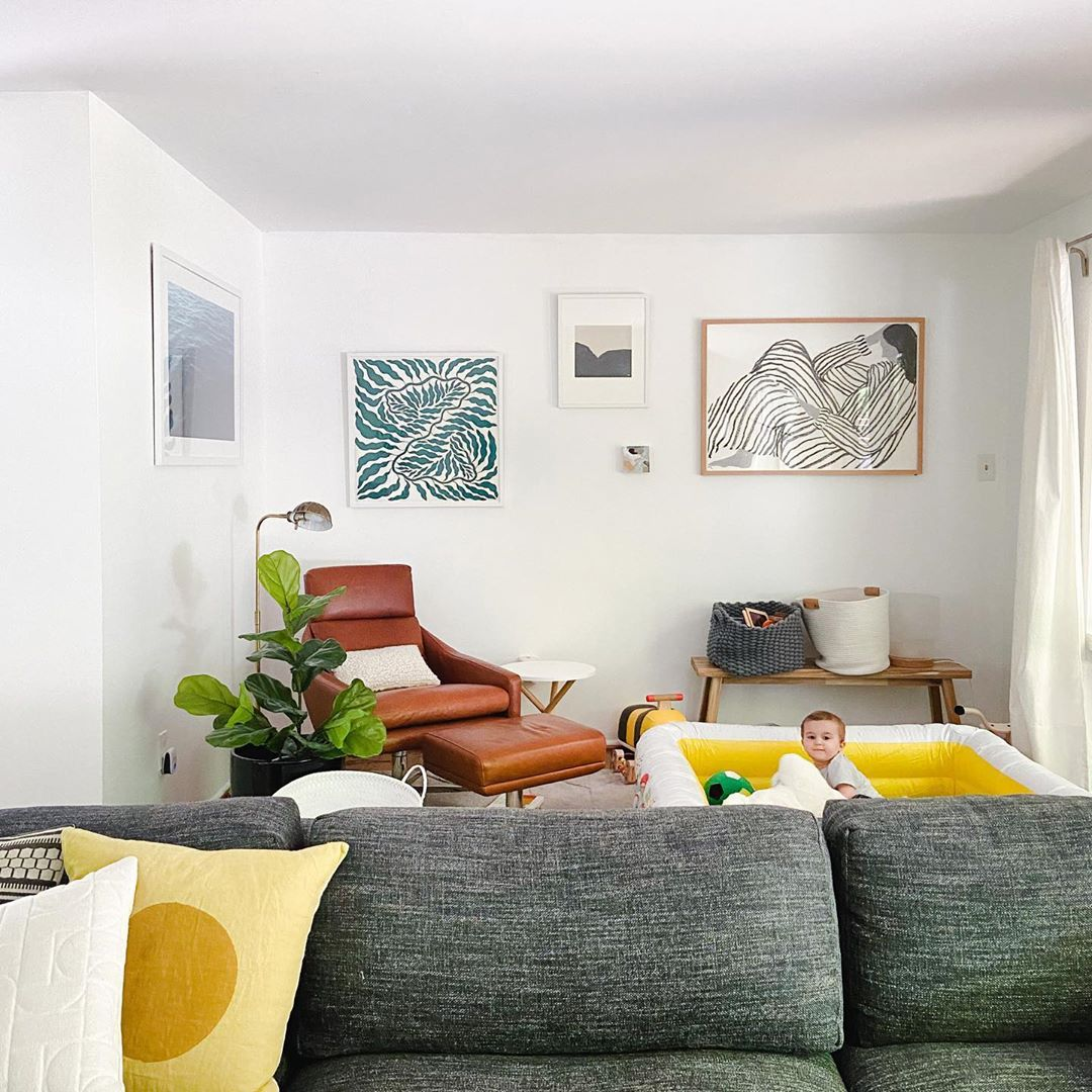 frames in living room with baby in kiddy pool