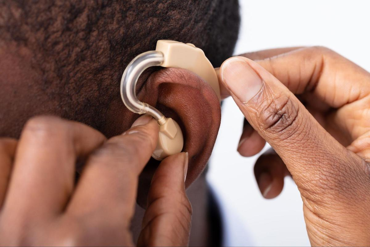 Person putting a hearing aid on another person's ear