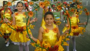 Foto de quatro meninas vestidas com vestidos amarelos e flores laranja no cabelo, todas segurando bambolês cheio de flores penduradas.