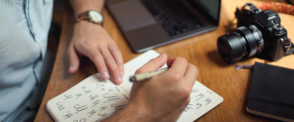 Man sketching out logo designs