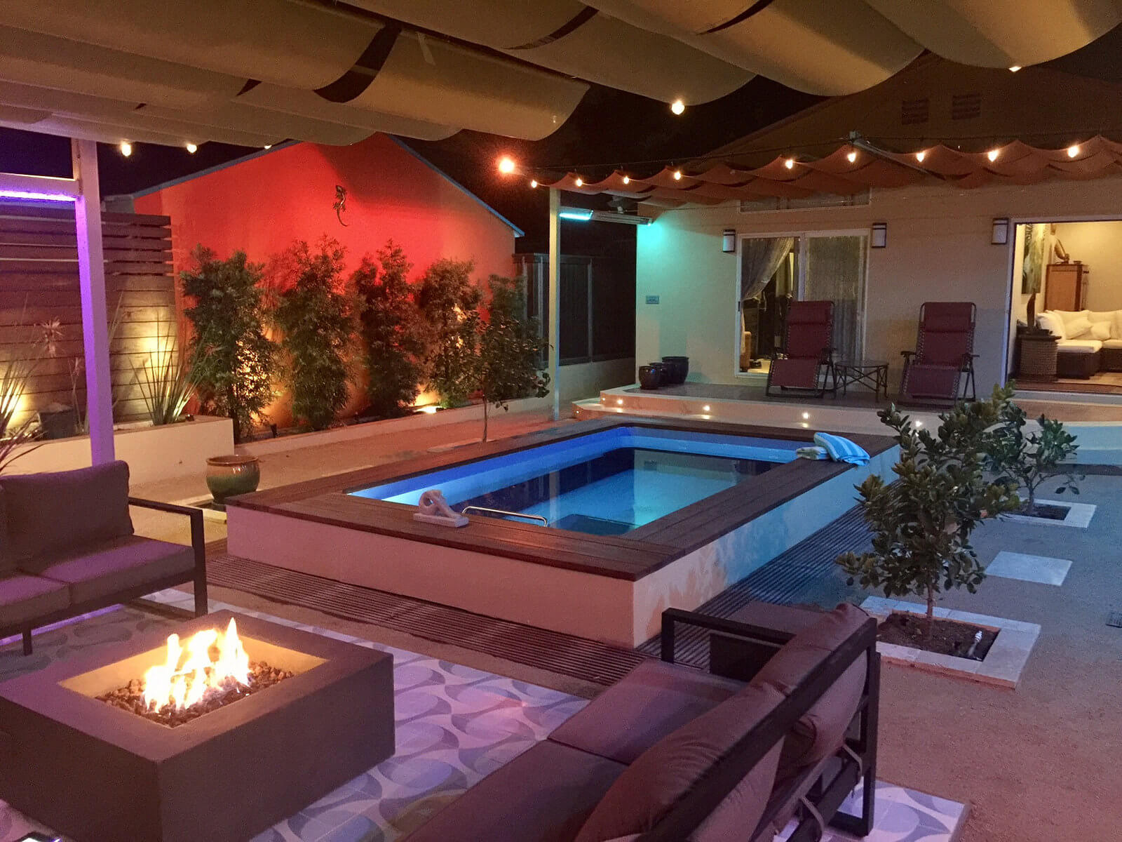 partially in-ground Original Endless Pool with a firepit and decorative lighting