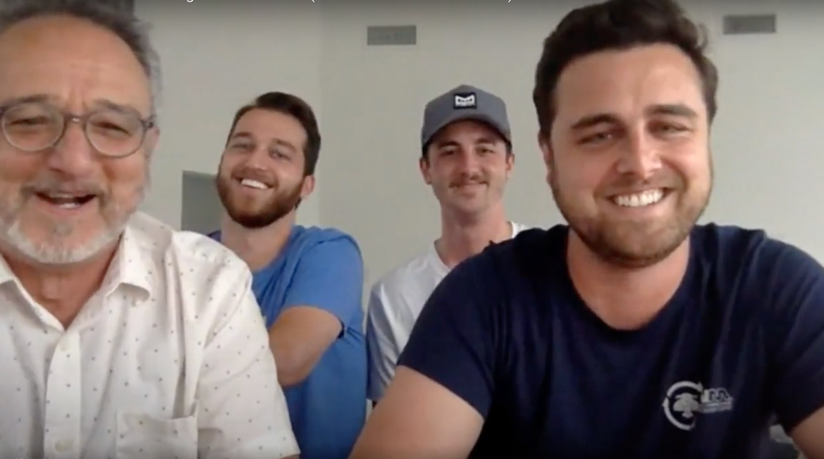 four men smiling on zoom computer screen call