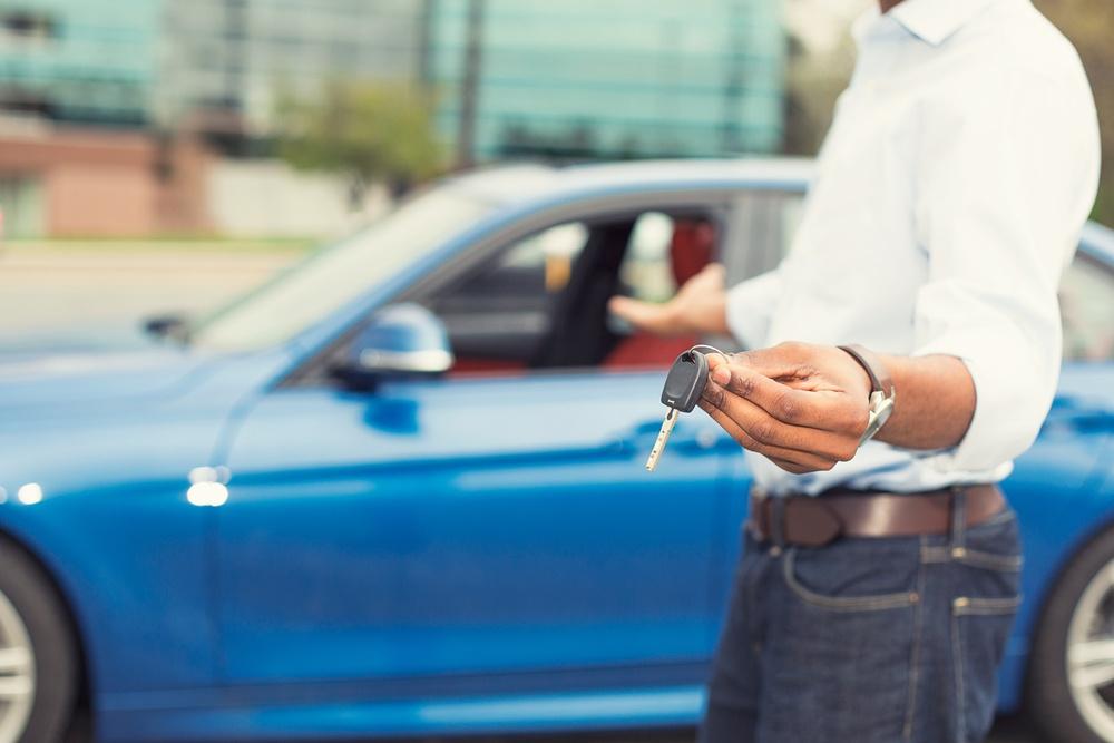 man holding keys outside a car