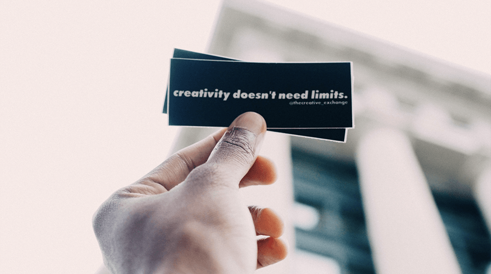 Person holding Creativity Doesn't Need Limits sticker