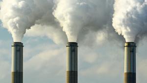 Foto de três chaminés de usinas, somente da parte de cima delas, com bastante fumaça saindo de todas.