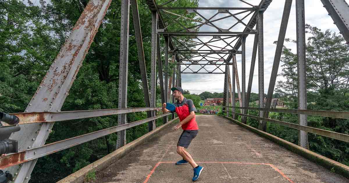 A disc golfer in the middle of throwing a tee shot on an old metal and concrete bridge