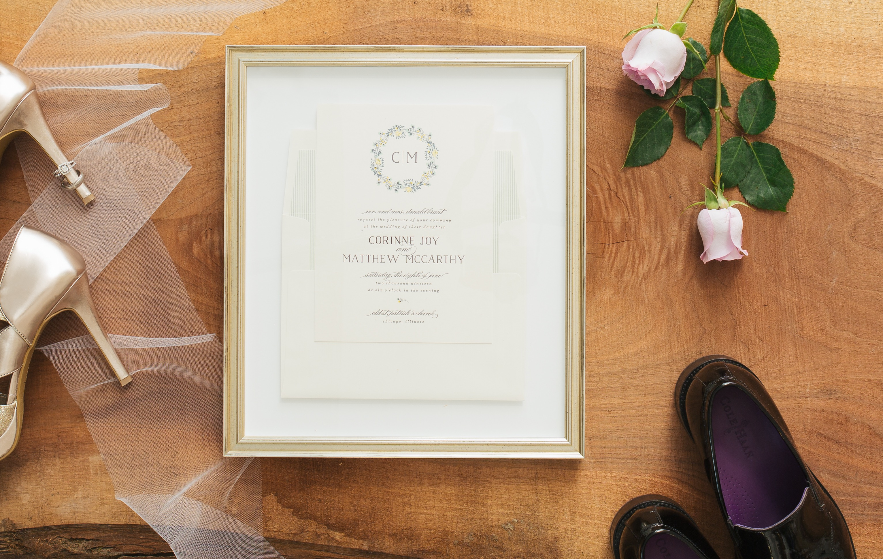 framed wedding invitation on wood table