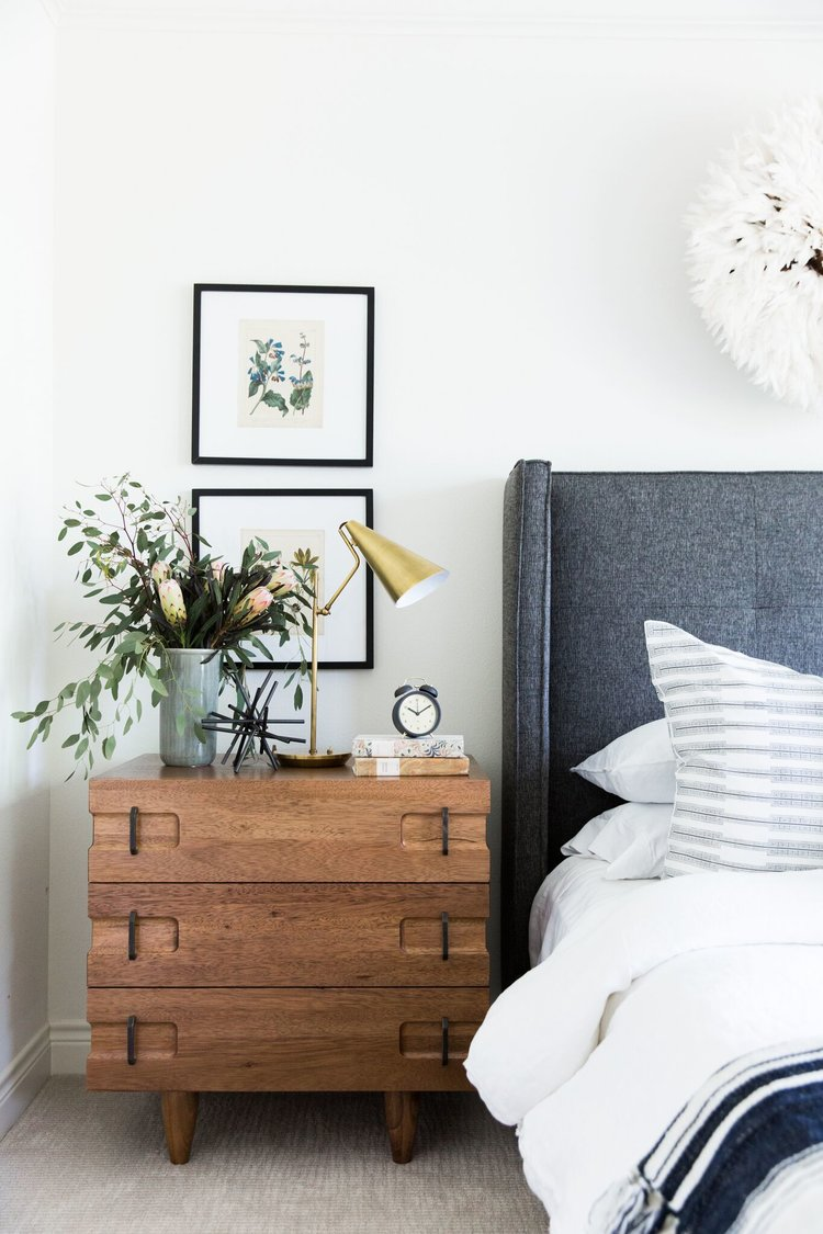 bedside with two frames above the nightstand