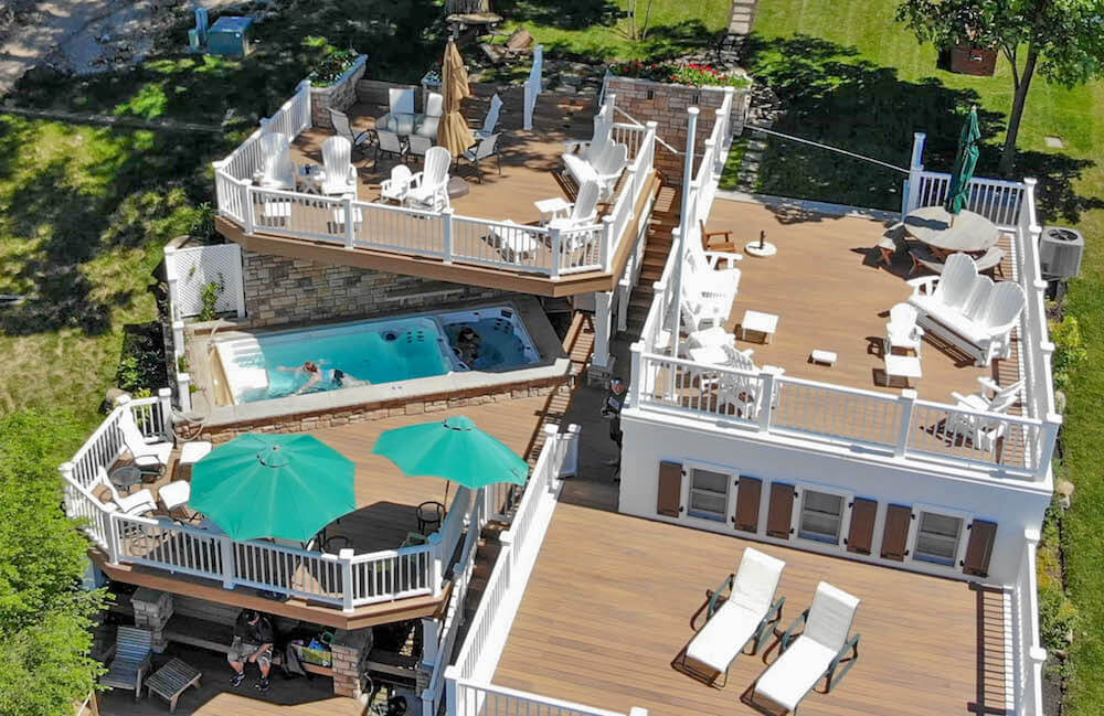 a drone shot of a house with multiple decks and an Endless Pools swim spa