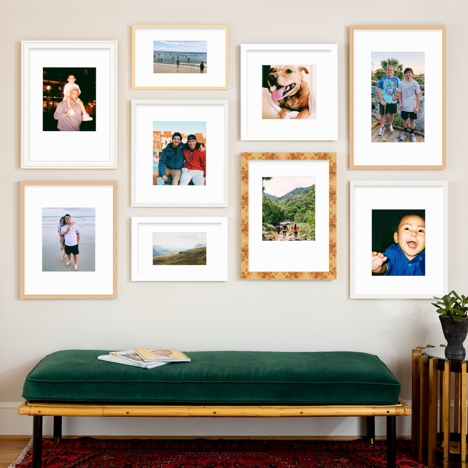staggered gallery wall in wood and white frames