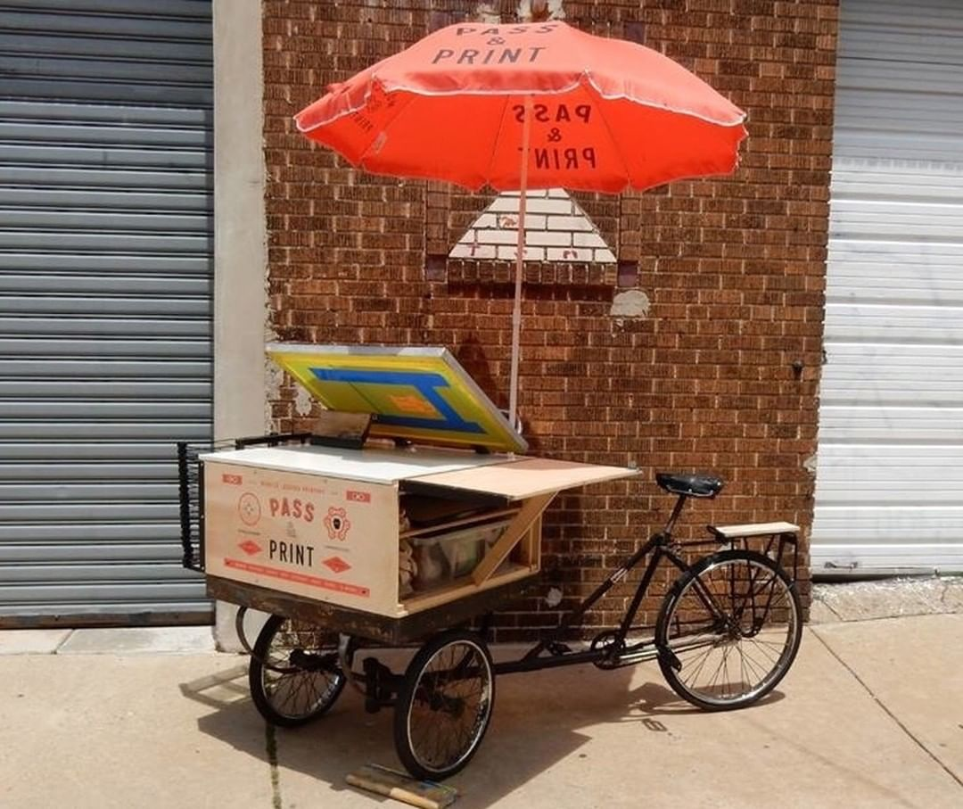 A screen printing setup on a three-wheeled bicycle