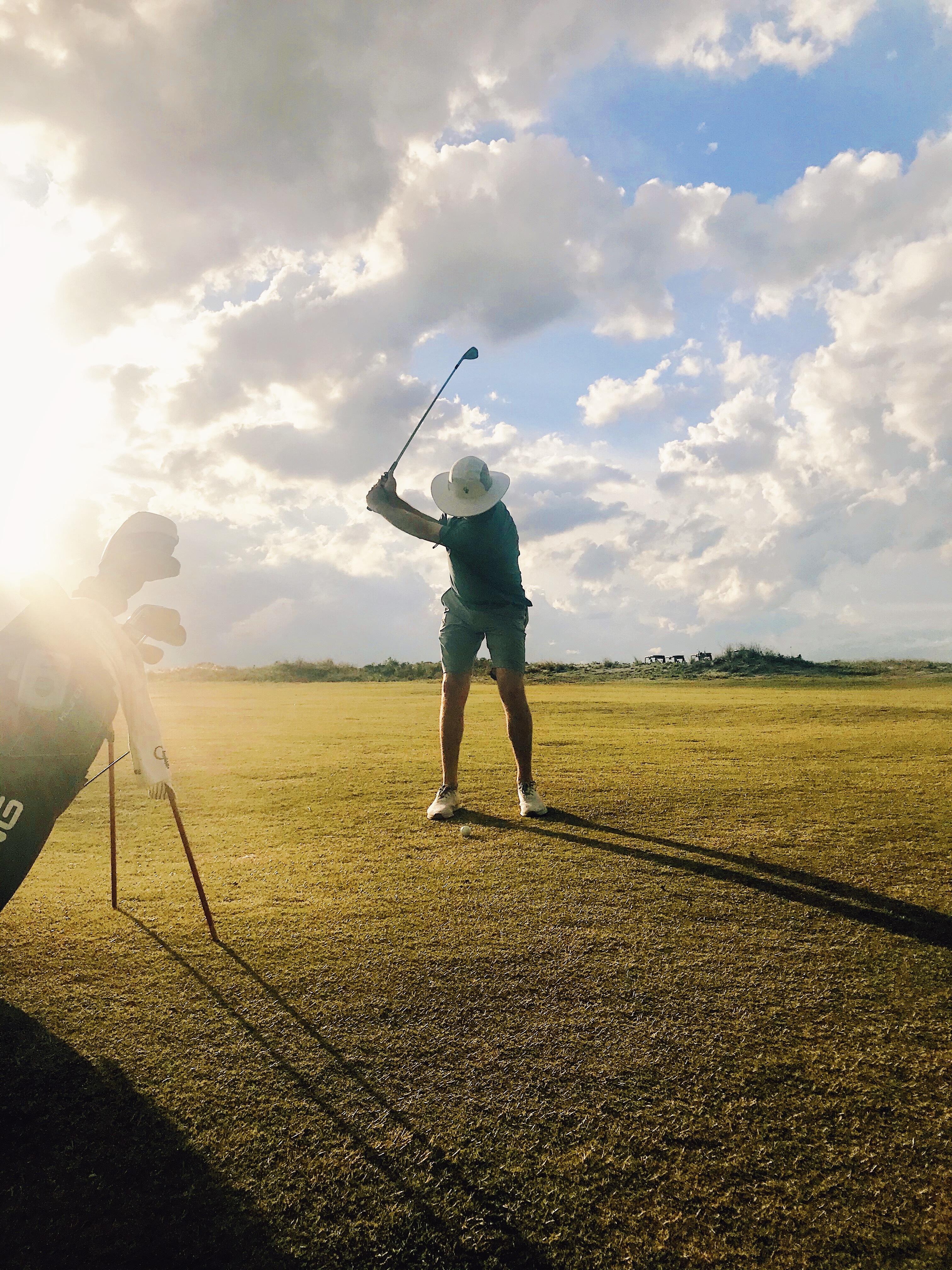 man swinging golf club in setting sun