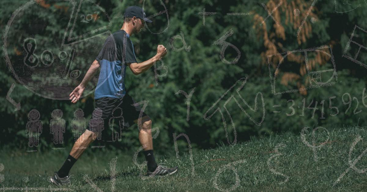 A man in shorts pumps his fist as he walks on a grassy area in front of trees