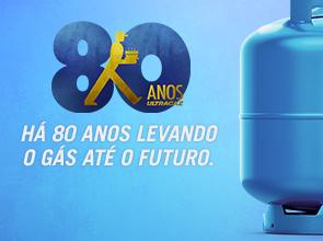 """Ilustração de fundo azul claro com botijão azul mais escuro à direita. Do lado esquerdo está escrito: """"Há 80 anos levando o gás até o futuro"""" com o número 80 grande e o esforçadinho, símbolo da Ultragaz que representa o vendedor de gás, centralizado no meio na cor dourada."""