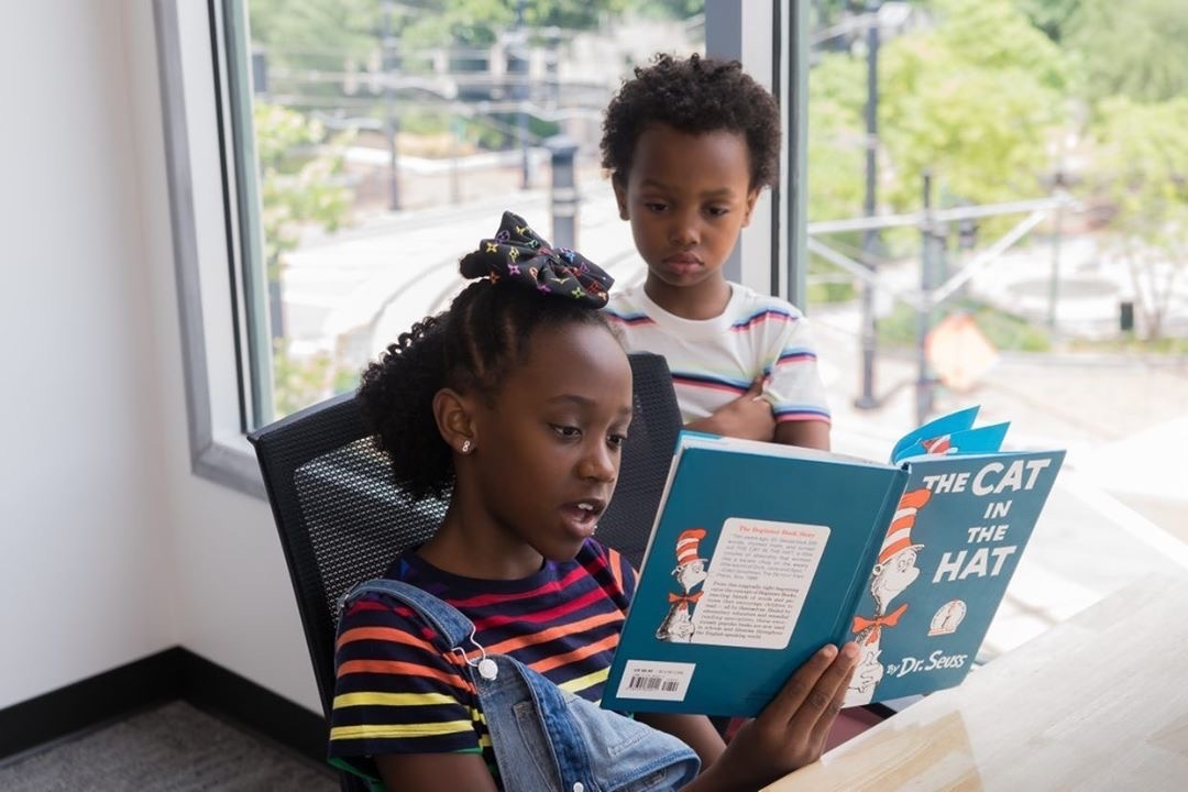 kids reading a book in primary t-shirts