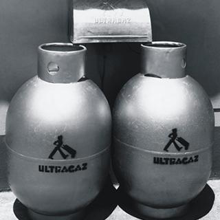 Foto em preto e branco dos primeiros botijões de 13kg da Ultragaz com logo estampado. Eram pratas de logo mais escuro.